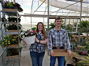 Two agriculture students pose at Bloomers Greenhouse.